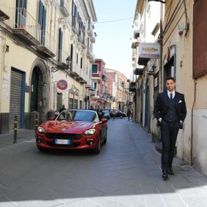 Sposo cammina in strada con lamborghini rossa