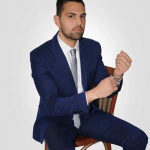 Abito sartoria uomo blu con cravatta seduto 2